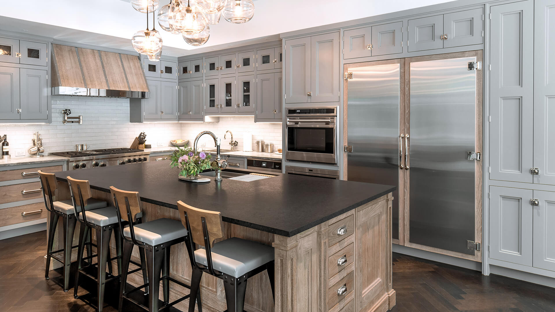Classic style kitchen with high-end nickel finishes with a walnut range hood equipped with polished nickel band and straps. Inset appliance and glass doors and walnut back