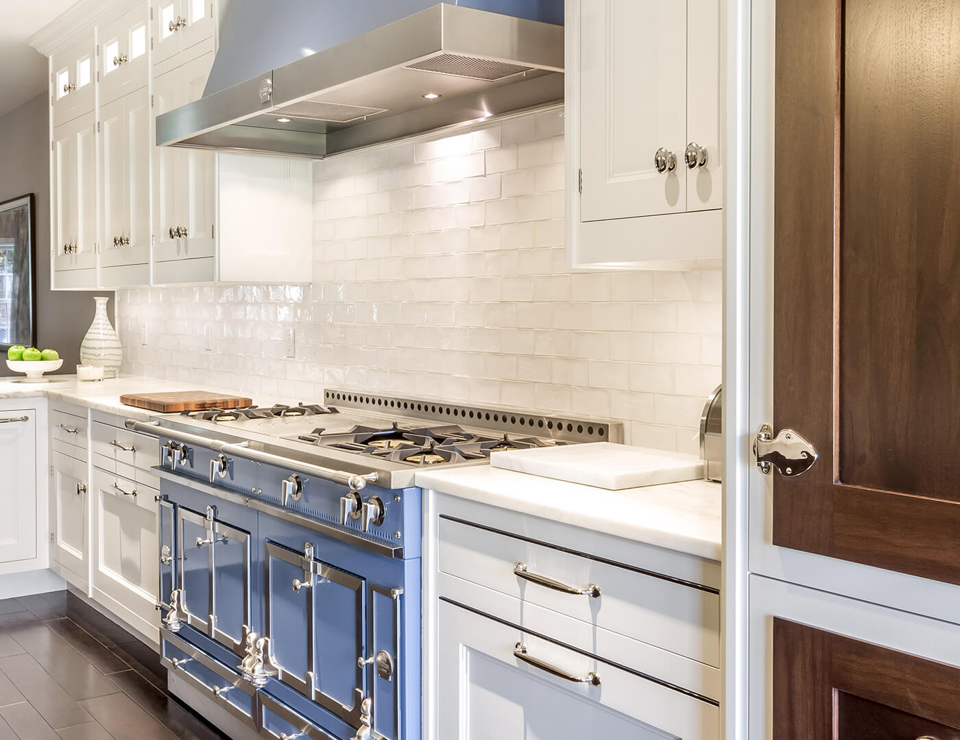 Beautiful range hood, stained walnut fridge doors, White cabinets, with polished nickel finishes