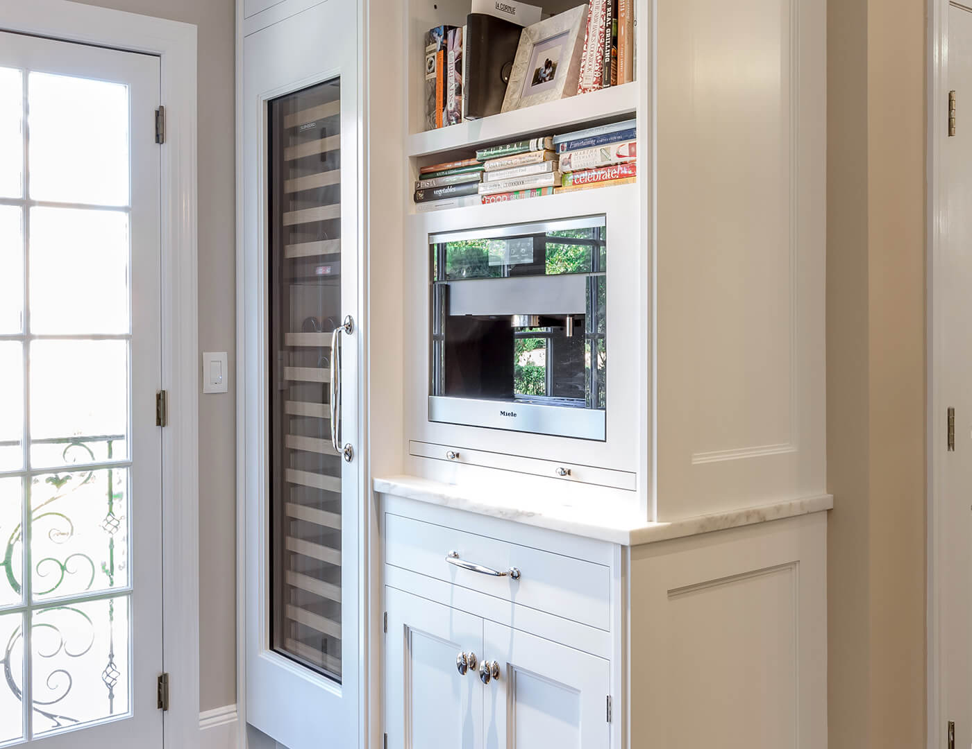 Prime white fitted custom cabinets with, polished nickel and custom wine chiller cabinet