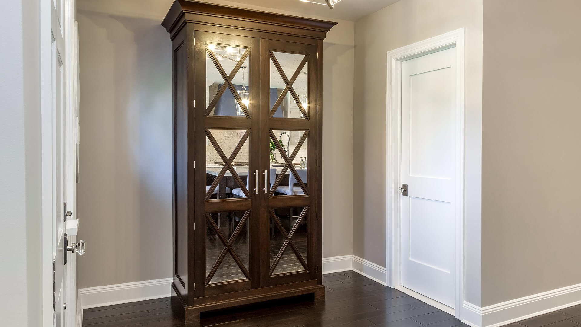 Stand alone pantry with stained walnut and antique mirror panel doors