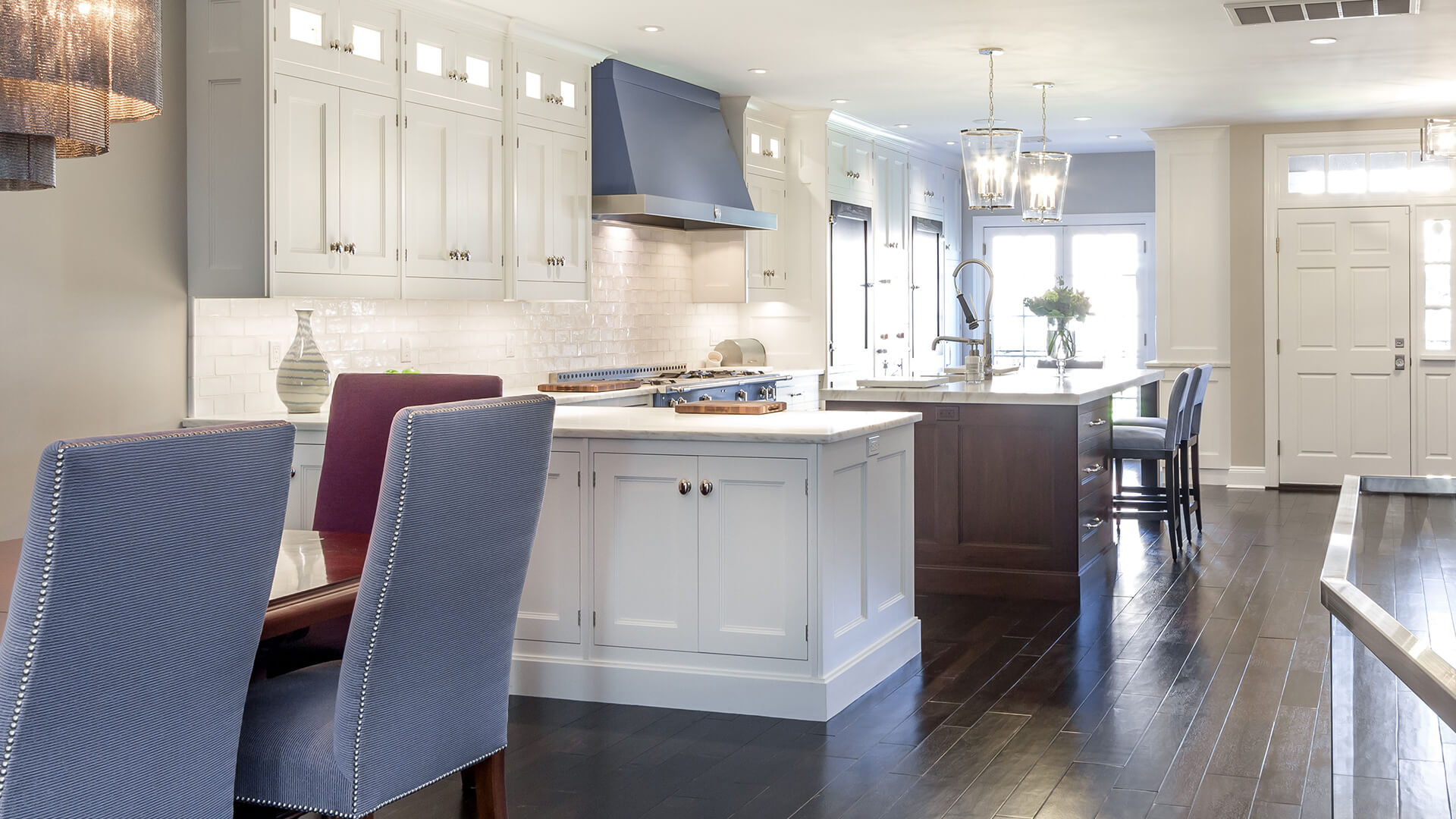 Upscale Custom kitchen with white handcrafted cabinets, stained walnut island, polished nickel finishes, and recessed lighting