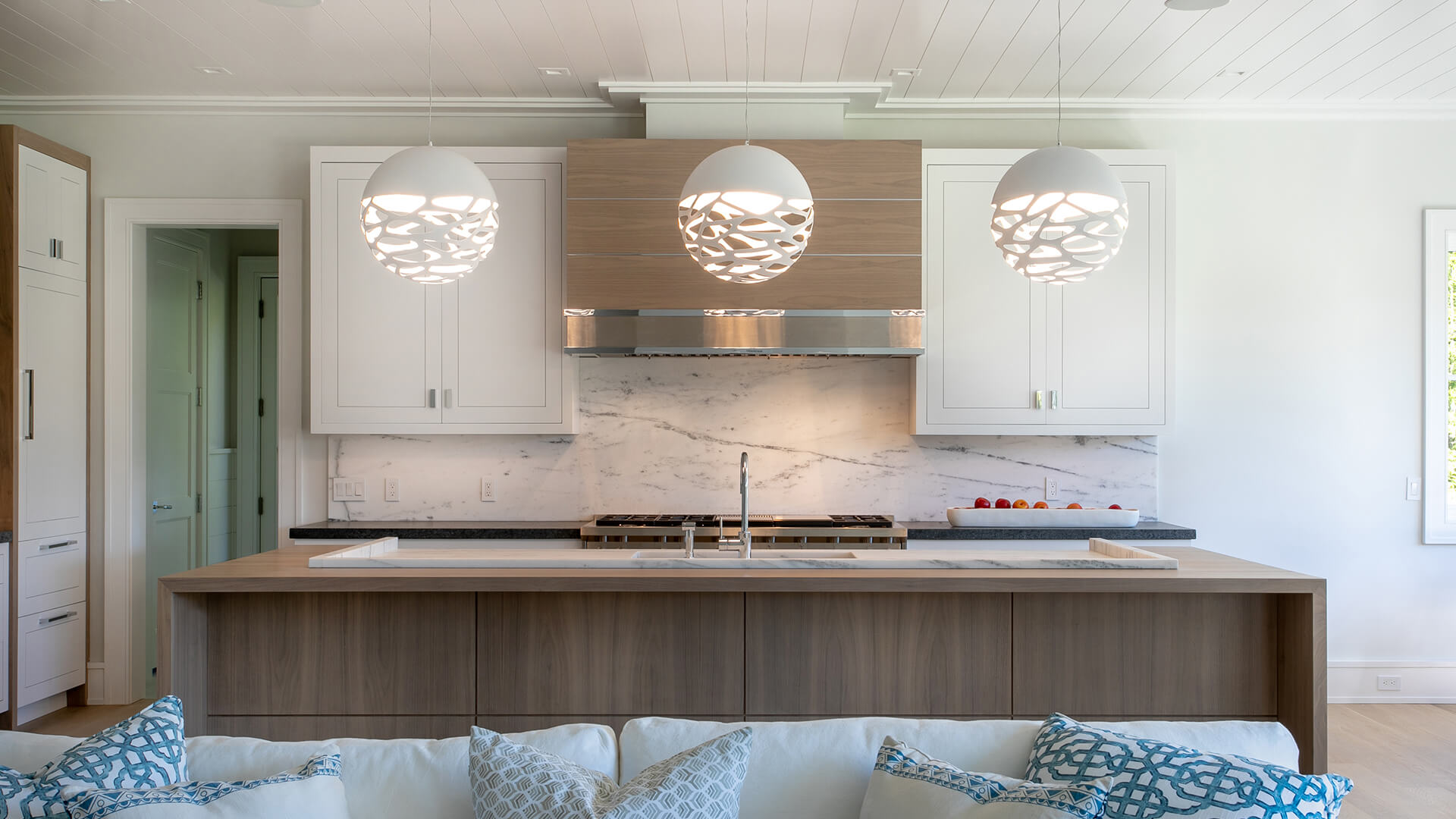 Front facing BK signature stained walnut drawer fronts and accents, a custom designed polished nickel /walnut rangehood and a stunning walnut waterfall countertop