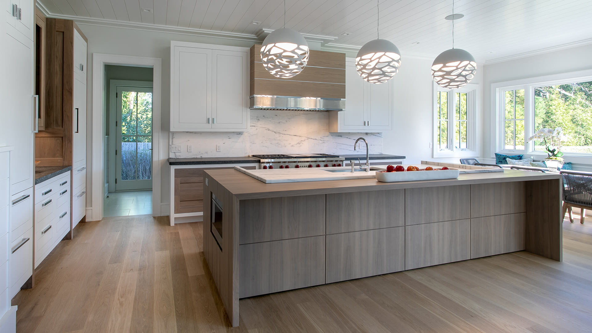 Upscale walnut island with a splash of quart, a custom designed polished nickel /walnut rangehood and a stunning walnut waterfall countertop with microwave inset. Wolf appliances and walnut cabinets with glass panels